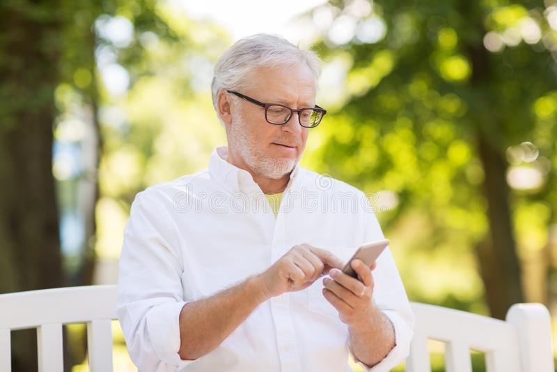 Hombre mayor con smartphone en el parque del verano foto de archivo