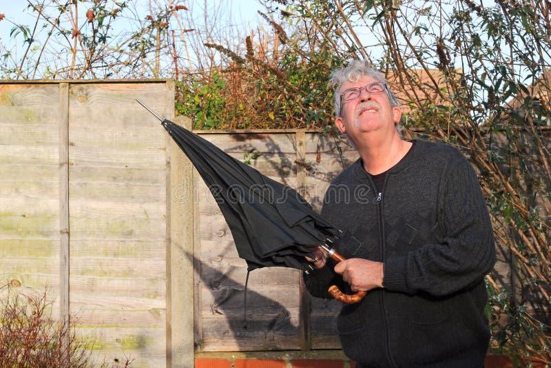 Hombre mayor con un paraguas que mira para arriba el cielo. imagen de archivo