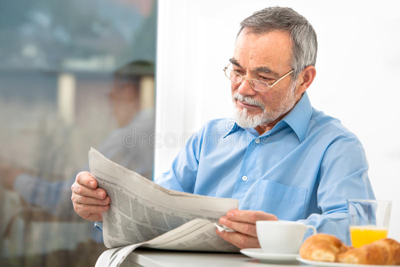 Hombre mayor con un periódico foto de archivo