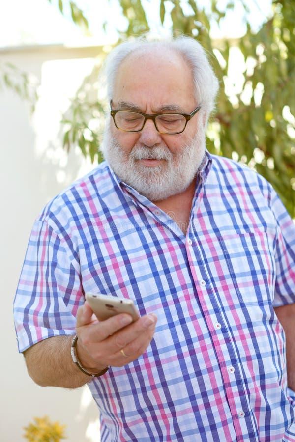 Hombre mayor con un smartphone imagenes de archivo