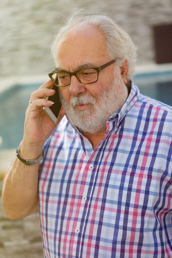 Hombre mayor con un smartphone imagen de archivo