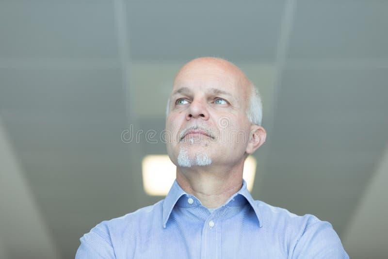 Hombre mayor con una expresión pensativa lejana fotografía de archivo libre de regalías