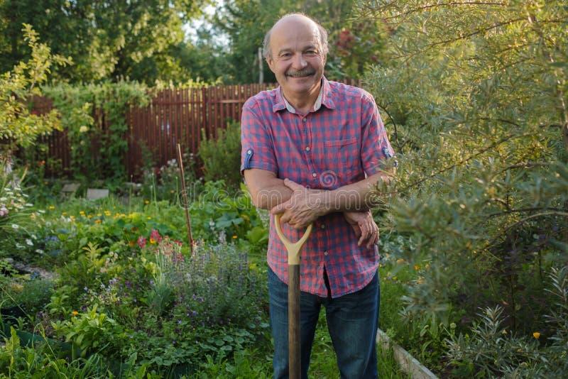 Hombre mayor con una situación del bigote en el jardín del verano, sonriendo fotografía de archivo libre de regalías