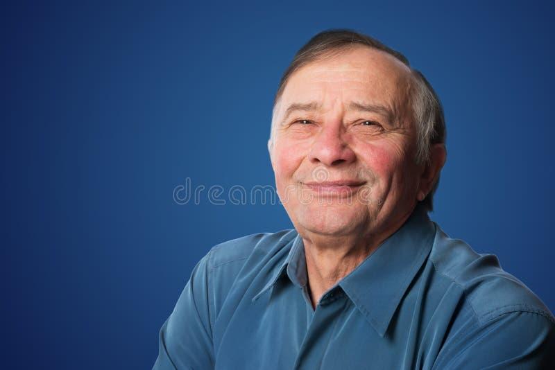 Hombre mayor con una sonrisa amistosa que se opone a vagos azul marino foto de archivo