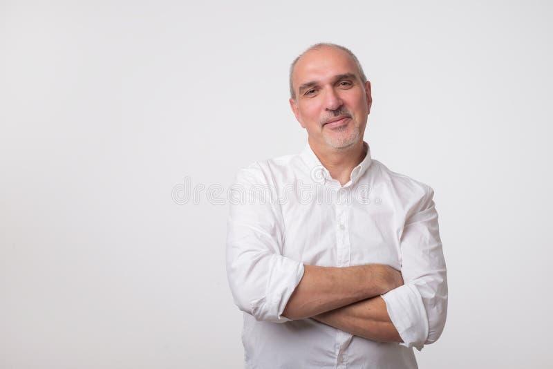 Hombre mayor confiado en las manos blancas de la travesía de la camiseta en pecho y mirada de la cámara imagenes de archivo