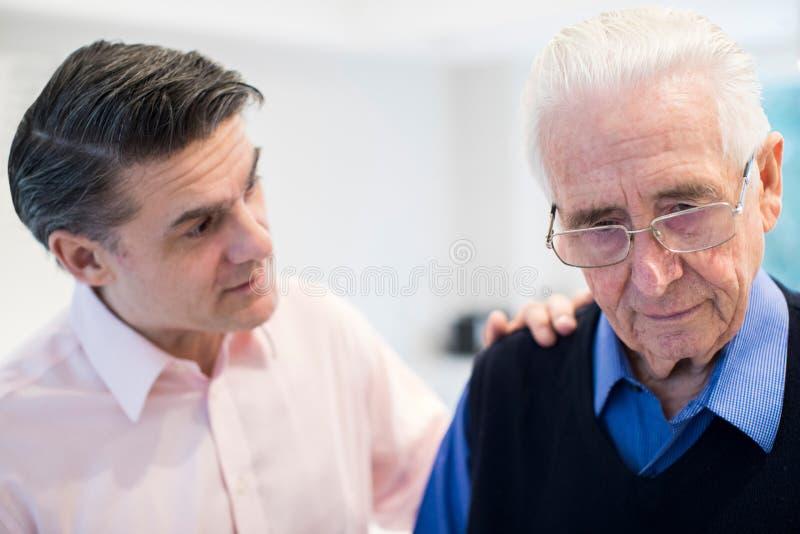 Hombre mayor confuso con el hijo adulto en casa imagenes de archivo