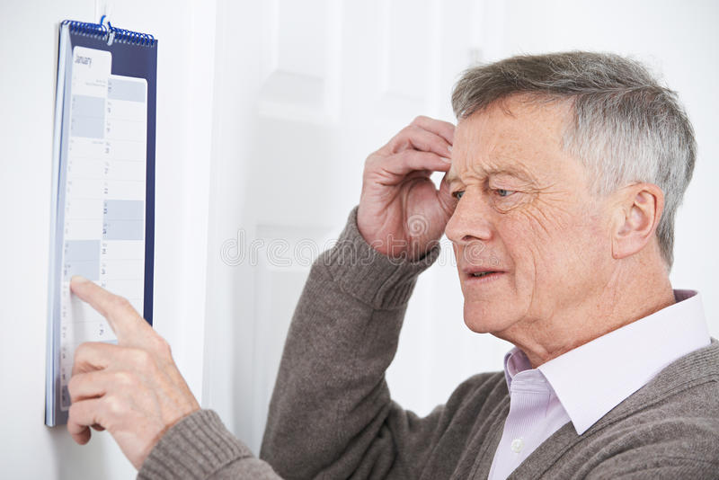 Hombre mayor confuso con la demencia que mira el calendario de pared imagen de archivo