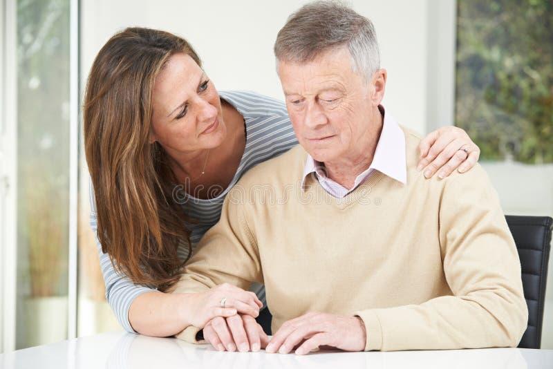 Hombre mayor confuso con la hija adulta en casa fotografía de archivo libre de regalías