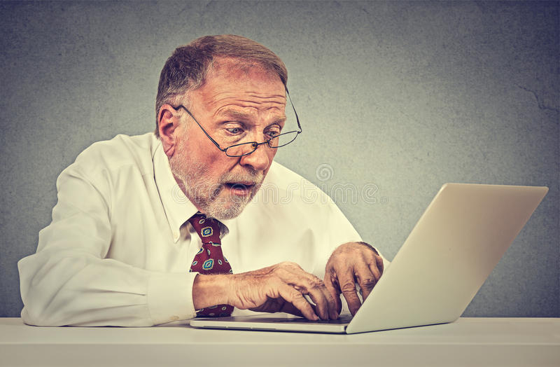 Hombre mayor confuso que usa un ordenador portátil de la PC imagen de archivo libre de regalías