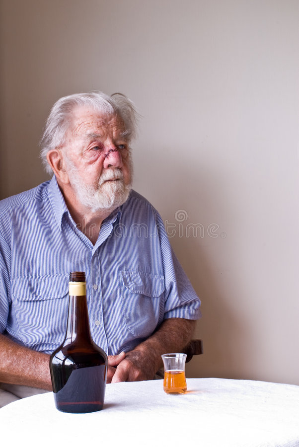 Hombre mayor contemplativo con la botella y el vidrio fotografía de archivo