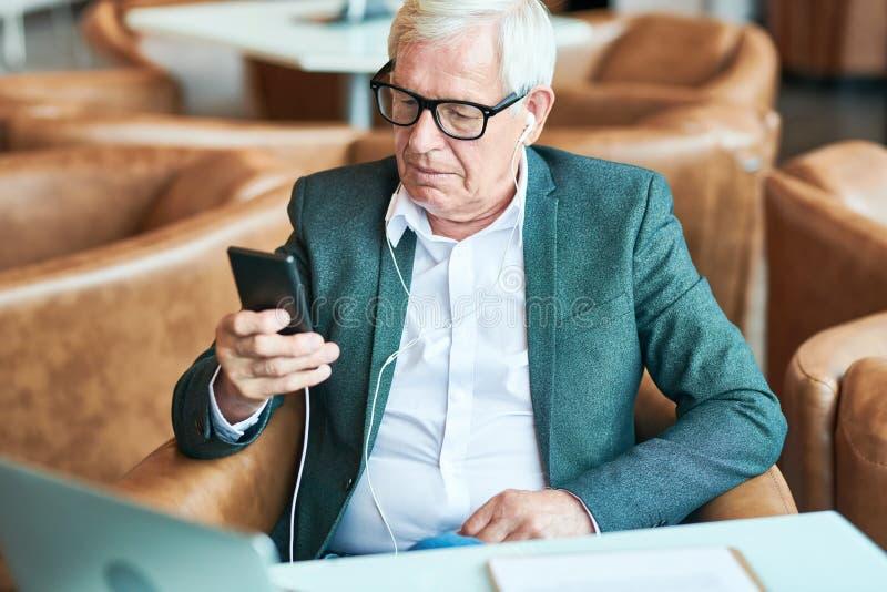 Hombre mayor contemporáneo que usa Smartphone en café imágenes de archivo libres de regalías