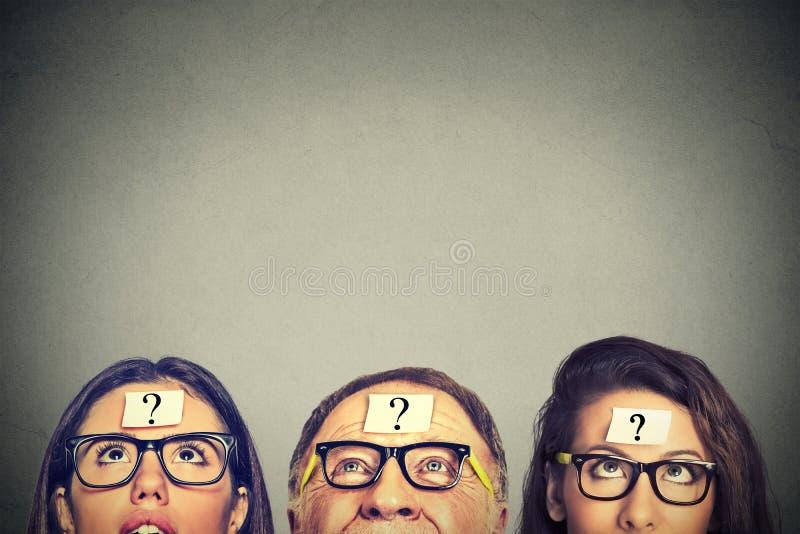 Hombre mayor de las mujeres jovenes del grupo de personas con el signo de interrogación que mira para arriba imagen de archivo libre de regalías