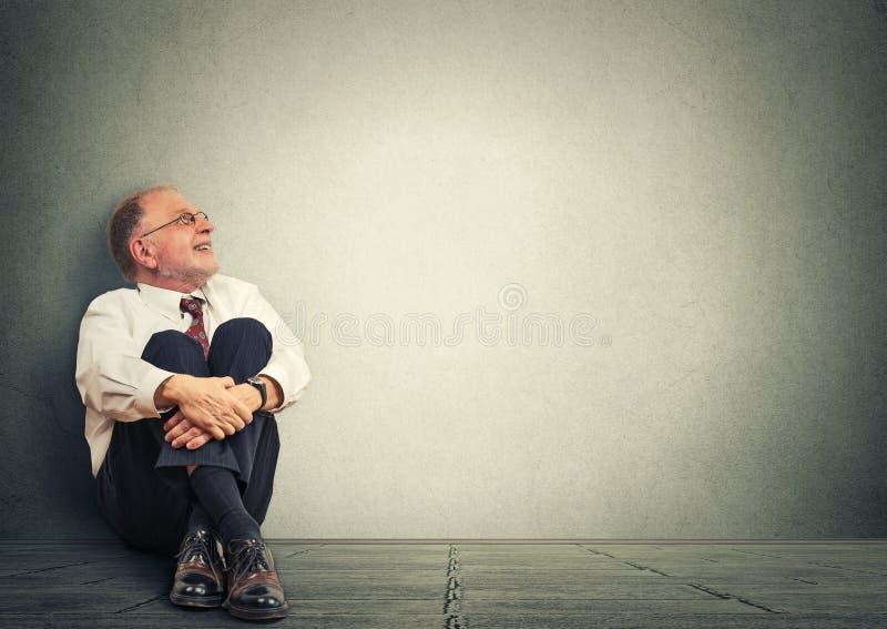 Hombre mayor de pensamiento que se sienta en piso Mirada sonriente del ejecutivo empresarial maduro para arriba de sueño fotografía de archivo libre de regalías