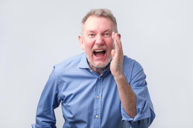Hombre mayor del líder en el grito azul de la camisa imagen de archivo