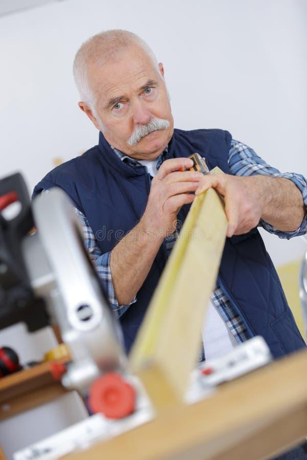 Hombre mayor del Midsection que toma la medida en el taller imágenes de archivo libres de regalías