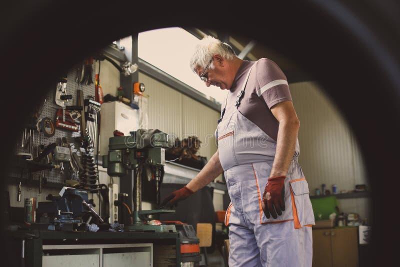 Hombre mayor del trabajo en su taller imágenes de archivo libres de regalías