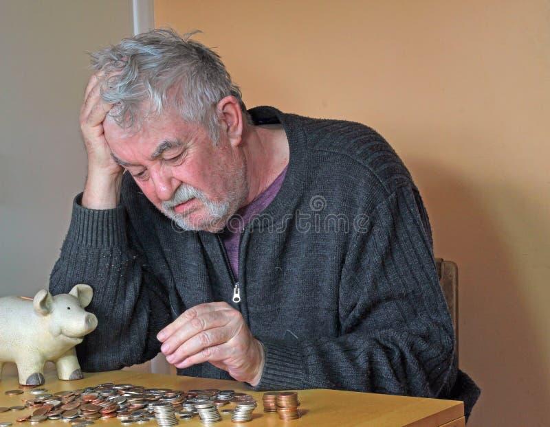 Hombre mayor deprimido que cuenta el dinero. imagen de archivo
