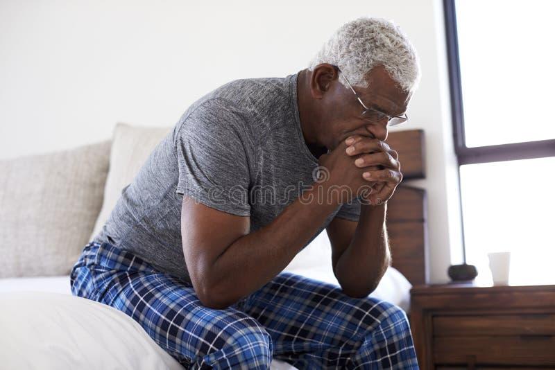 Hombre mayor deprimido que mira la sentada infeliz en el lado de la cama en casa con la cabeza en manos imágenes de archivo libres de regalías
