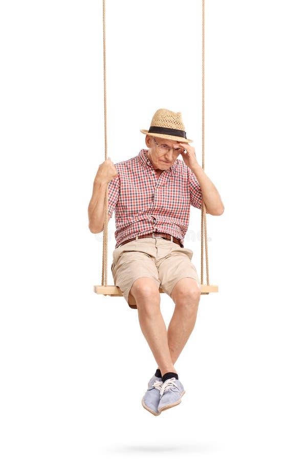 Hombre mayor deprimido que se sienta en un oscilación imagenes de archivo