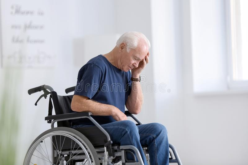 Hombre mayor discapacitado en el sufrimiento de la silla de ruedas del dolor de cabeza en casa fotos de archivo