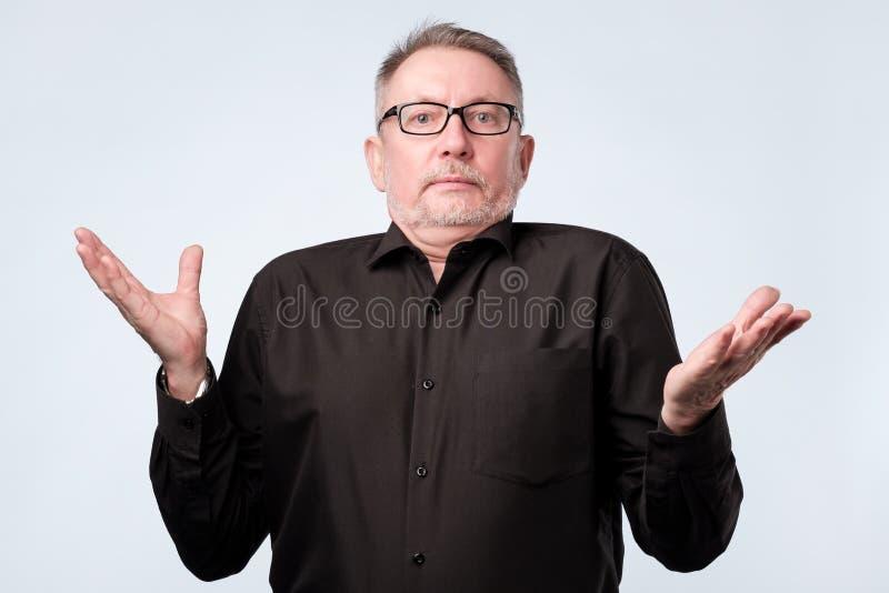 Hombre mayor dudoso en duda y la sensaci?n insegura imagen de archivo libre de regalías