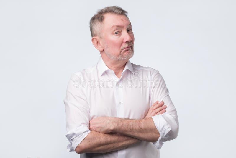 Hombre mayor dudoso que mira con la expresión de la incredulidad foto de archivo libre de regalías