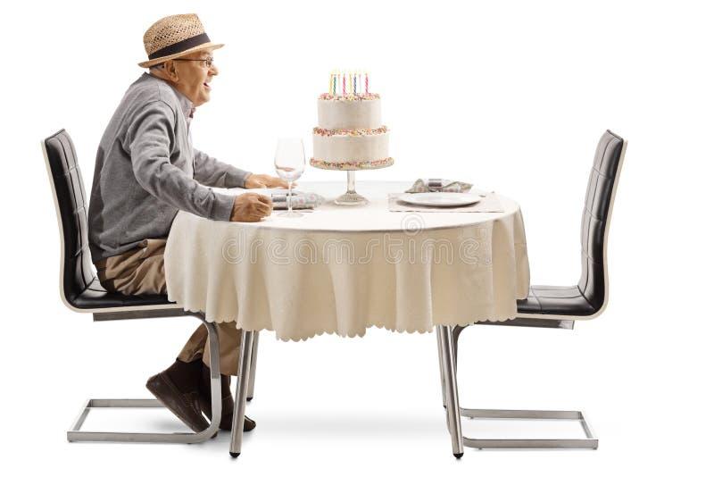 Hombre mayor emocionado con una torta de cumpleaños en una tabla del restaurante fotografía de archivo libre de regalías