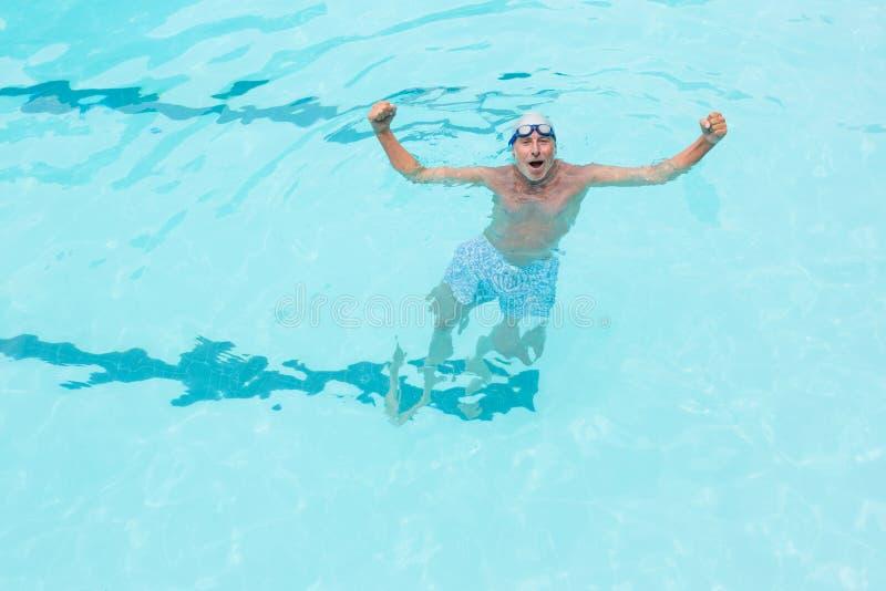 Hombre mayor emocionado que se coloca en piscina fotos de archivo