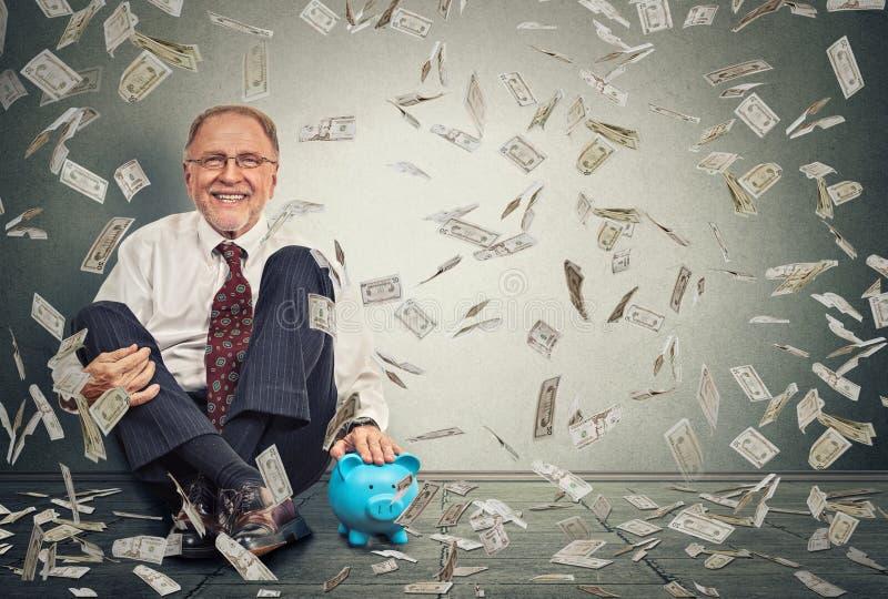 Hombre mayor emocionado que se sienta en un piso con la hucha debajo de una lluvia del dinero fotografía de archivo libre de regalías