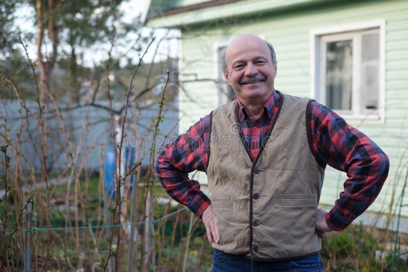 Hombre mayor en chaleco en el fondo de la casa en el pueblo foto de archivo