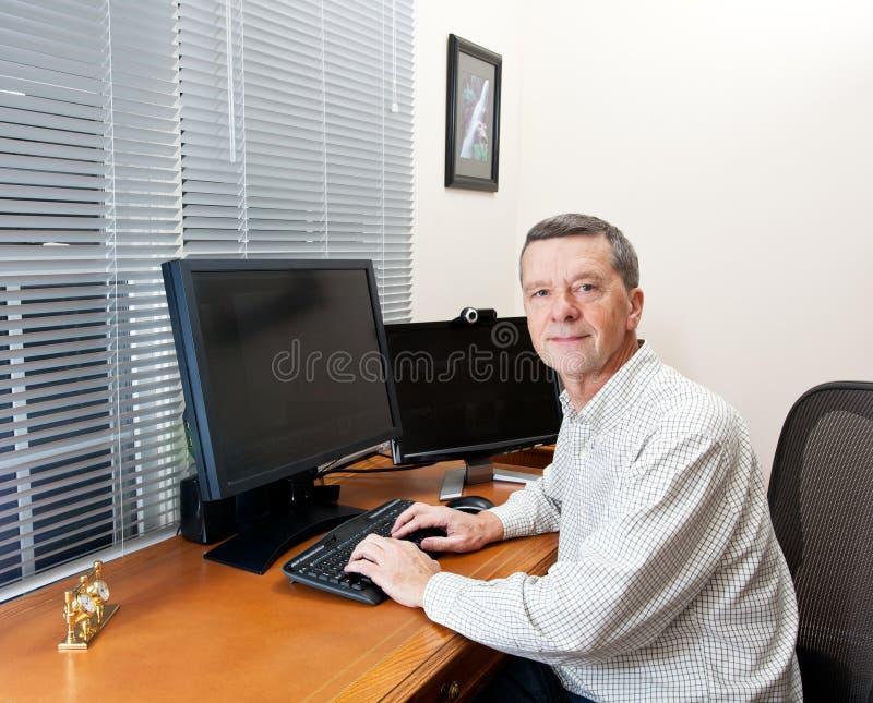 Hombre mayor en el escritorio del ordenador fotografía de archivo libre de regalías