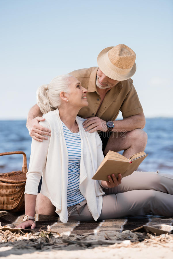 Hombre mayor en el sombrero que abraza a la mujer sonriente que se sienta en la tela escocesa y el libro de lectura fotografía de archivo libre de regalías