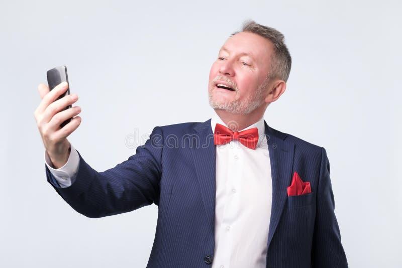 Hombre mayor en el traje azul que mira la pantalla del teléfono elegante, sonriendo agradable foto de archivo