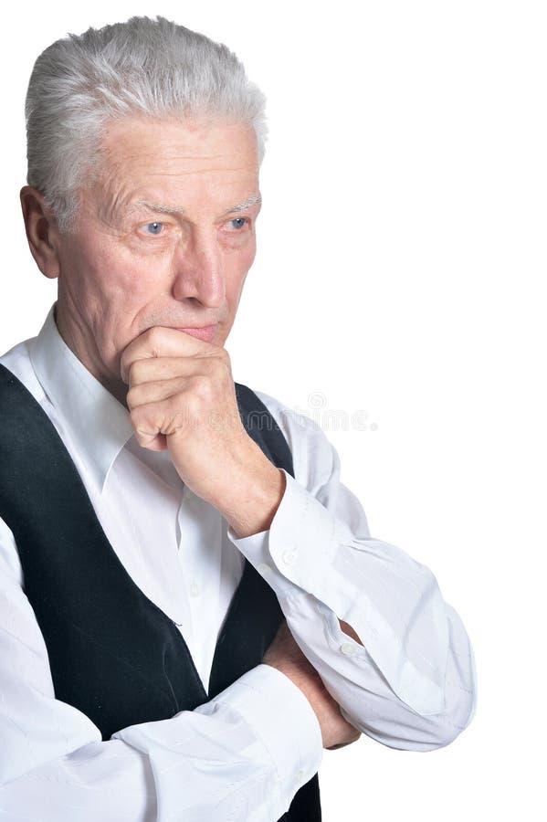 Hombre mayor en la chaqueta sin mangas negra que presenta en el fondo blanco imágenes de archivo libres de regalías