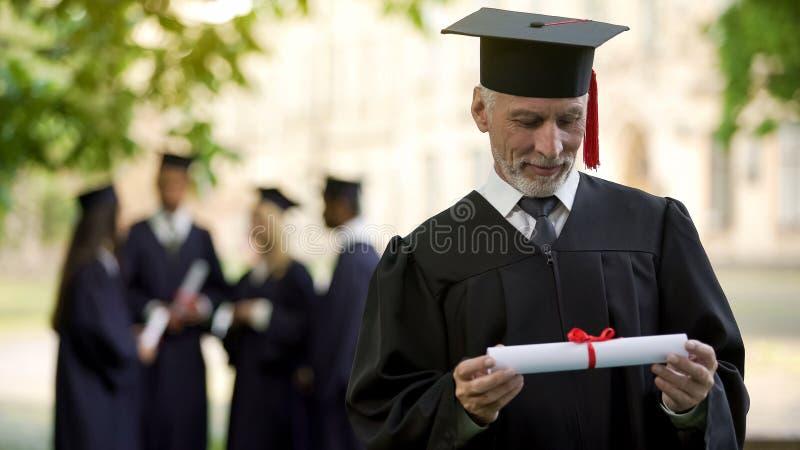 Hombre mayor en la regalía académica que sostiene el diploma, educación en cualquier edad, nuevo grado fotos de archivo