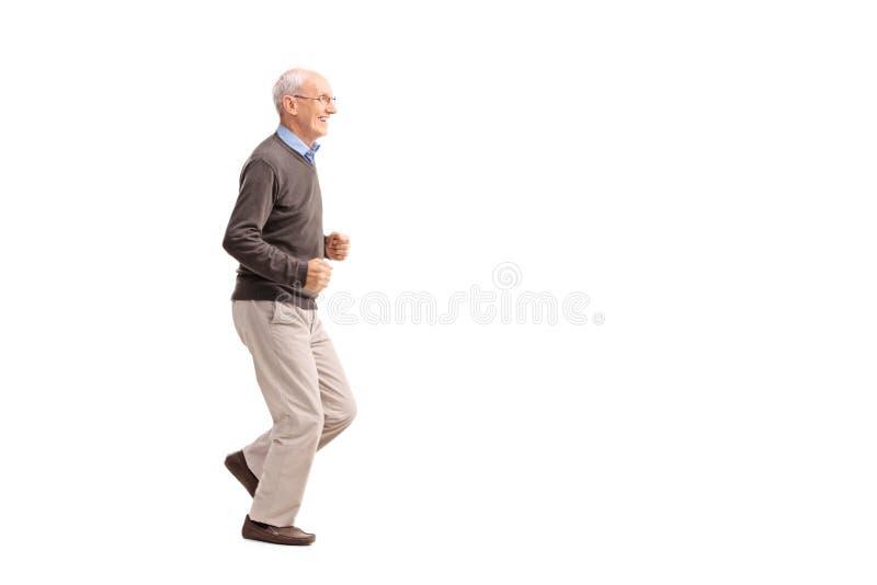 Hombre mayor en la ropa casual que corre y que sonríe imágenes de archivo libres de regalías