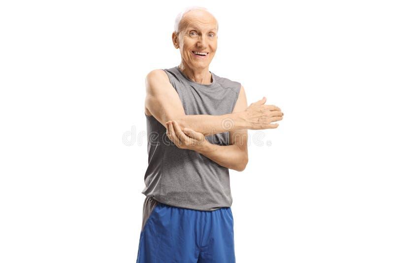 Hombre mayor en la ropa de deportes que estira su brazo imágenes de archivo libres de regalías