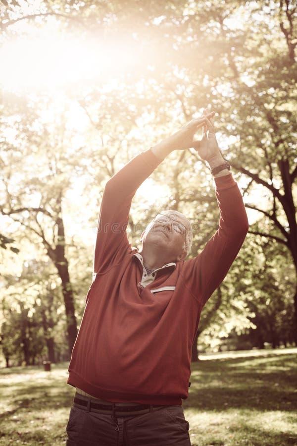 Hombre mayor en la ropa de los deportes que estira y que ejercita h imagen de archivo