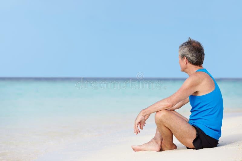 Hombre mayor en la ropa de los deportes que se relaja en la playa hermosa foto de archivo