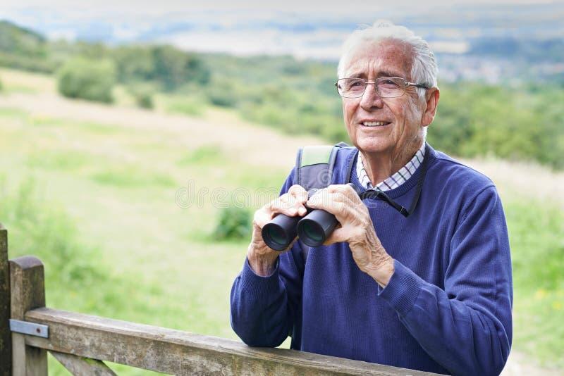 Hombre mayor en paseo con los prismáticos foto de archivo