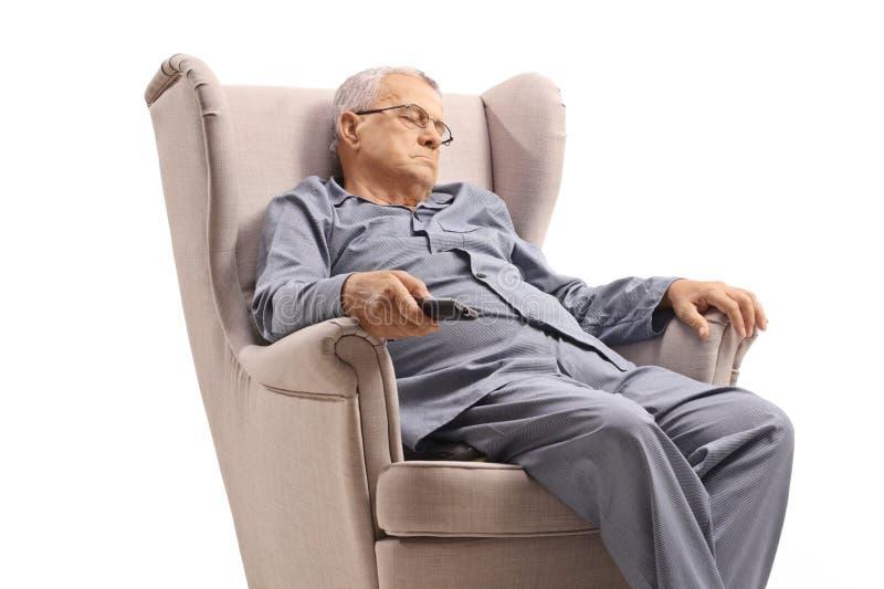 Hombre mayor en pijamas que duerme en una butaca y que sostiene un teledirigido fotografía de archivo