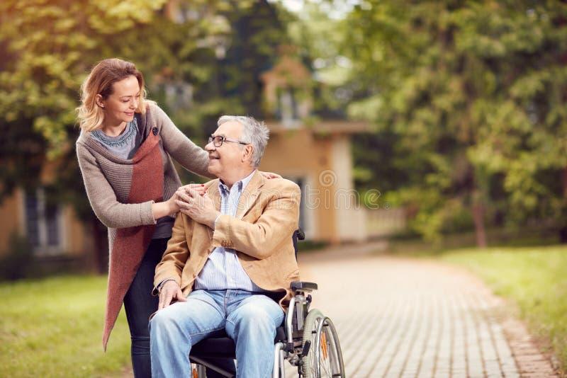 Hombre mayor en silla de ruedas con la hija del cuidador fotos de archivo libres de regalías