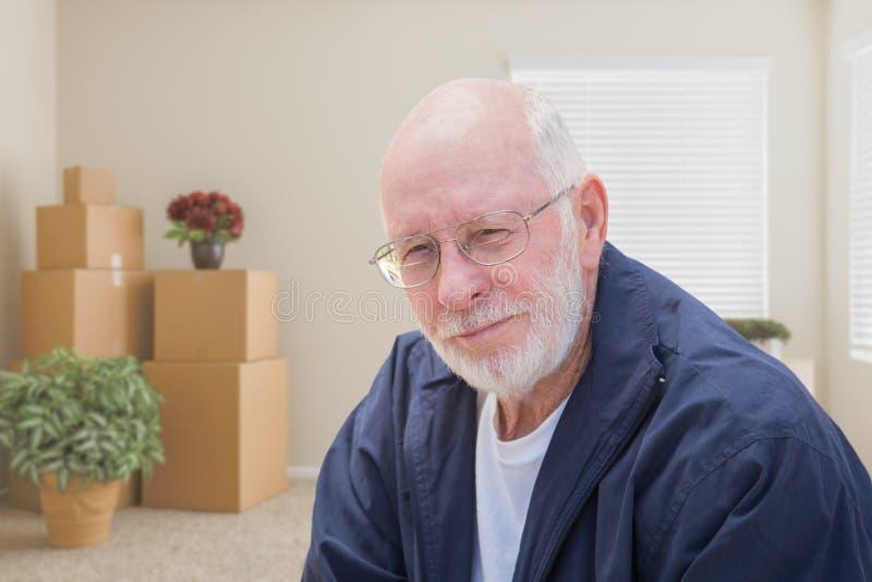 Hombre mayor en sitio vacío con las cajas móviles llenas fotos de archivo