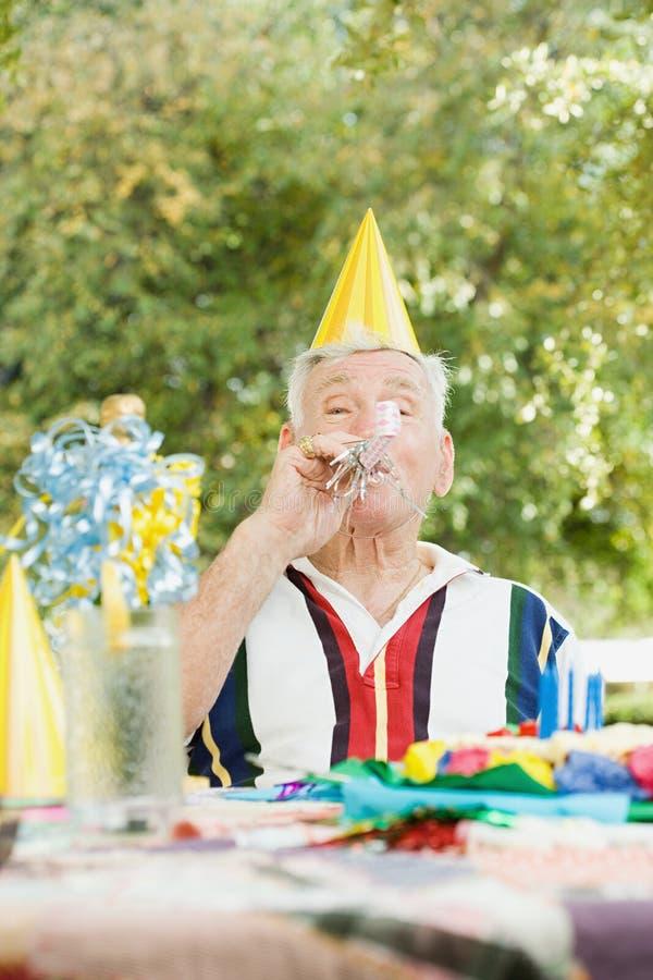 Hombre mayor en una fiesta de cumpleaños imagenes de archivo