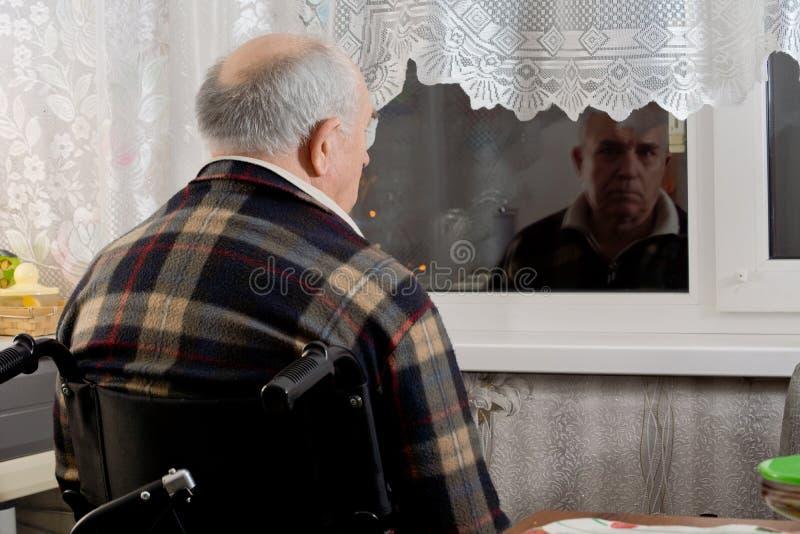 Hombre mayor en una silla de ruedas que espera en una ventana fotos de archivo