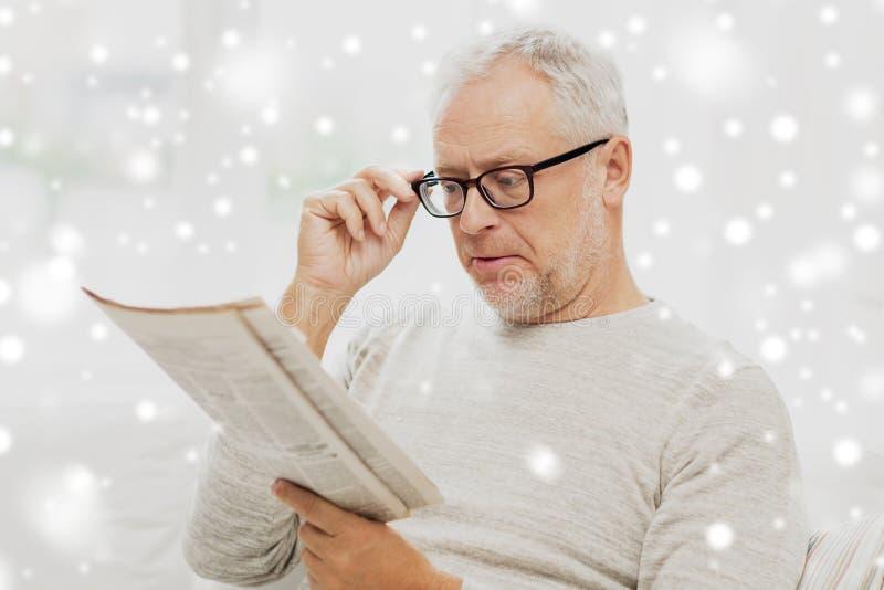 Hombre mayor en vidrios que lee el periódico sobre nieve fotografía de archivo