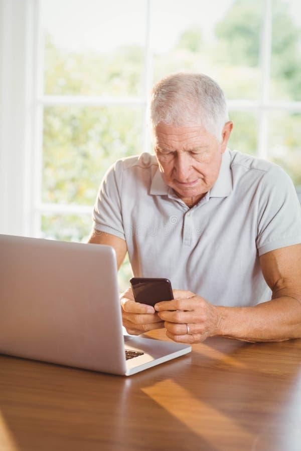 Hombre mayor enfocado que usa smartphone y el ordenador portátil imagenes de archivo