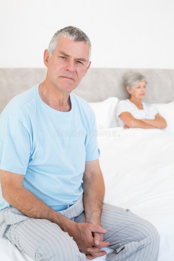 Hombre mayor enojado en cama con la mujer en fondo imagen de archivo