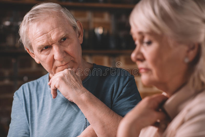 Hombre mayor enojado que mira en mujer del trastorno en casa fotos de archivo