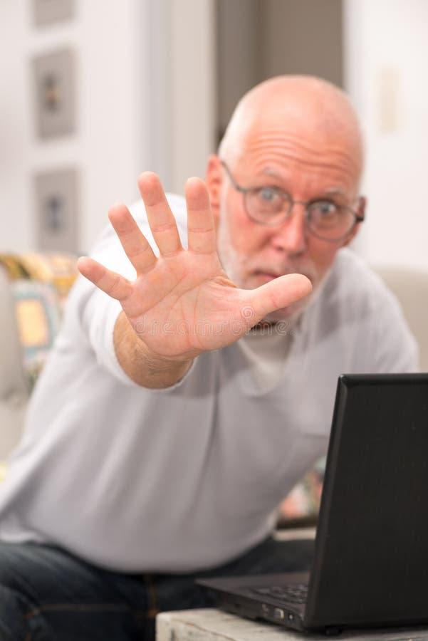 Hombre mayor enojado que usa un ordenador portátil en hogar imagenes de archivo